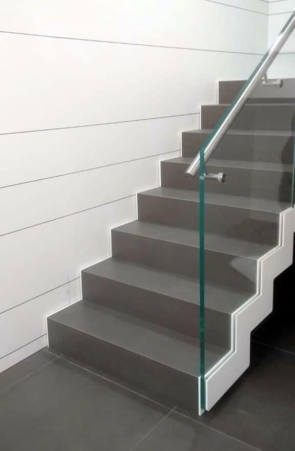 Escalera recta con baranda de cristal.